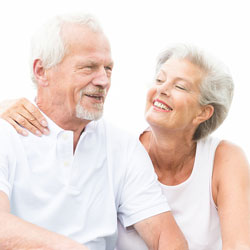 Älteres Ehepaar sitzt nebeneinander und lächelt