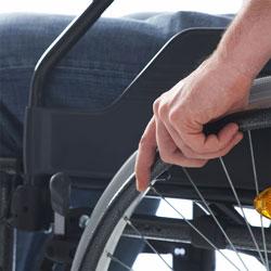 Rollstuhlfahrer hält seine Hand auf das linke Rad