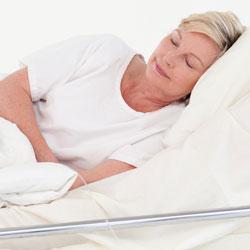 Frau liegt seitlich und leidet unter Wundliegen