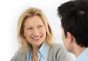 Blonde Frau sitzt einem Mann mit dunkeln Haaren gegenüber