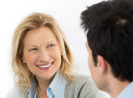 Blonde Frau sitzt Mann mit dunkeln Haaren gegenüber